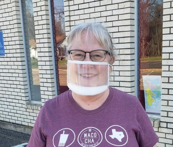 White woman wearing clear mask, glasses, and maroon T-shirt with Waco Cha logo